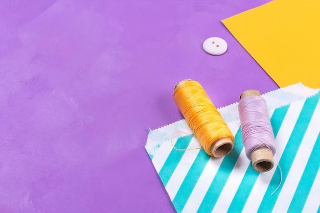 Nähen von gelben und purpurroten threads auf hellem hintergrund. kunst