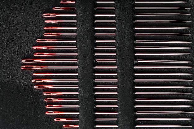 Nähen von nadeln verschiedener größen in einem satz von rot auf einem schwarzen hintergrund.