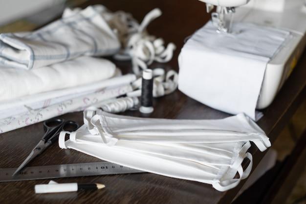 Nähen von schutzmasken zu hause. nähmaschine, schere und ein haufen fertiger masken