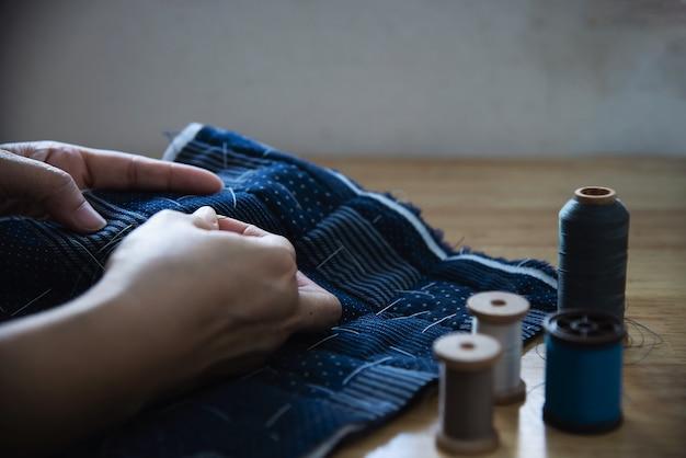 Nähender stoff der weinlesefrau eigenhändig mit stickerei stellte auf holztisch - leute und handgemachtes diy hausarbeitkonzept ein