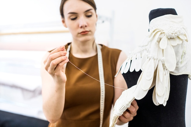 Nähendes kleid des weiblichen designers mit nadel