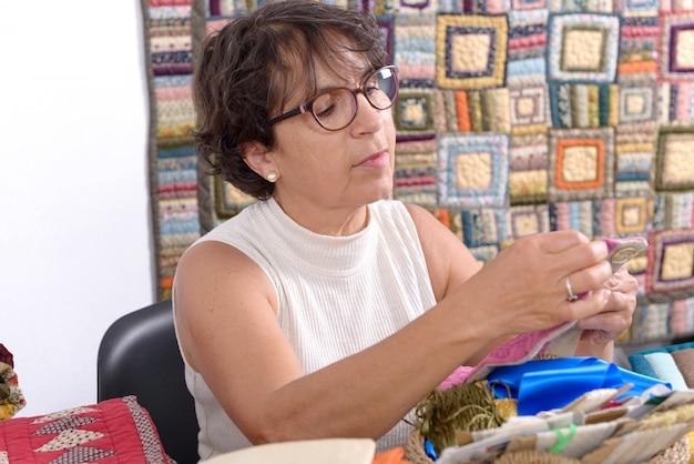 Nähendes patchwork der reifen brunettefrau