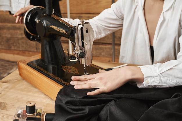 Näherin arbeitet an neuem projekt. weiblicher abwasserkanal, der mit stoff arbeitet, modisches kleidungsstück mit nähmaschine an ihrem arbeitsplatz schafft, sich auf nadel konzentriert, um naht ordentlich aussehen zu lassen