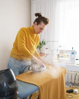 Näherin bügelt orangefarbenen stoff, während sie an ihrem arbeitsplatz arbeitet