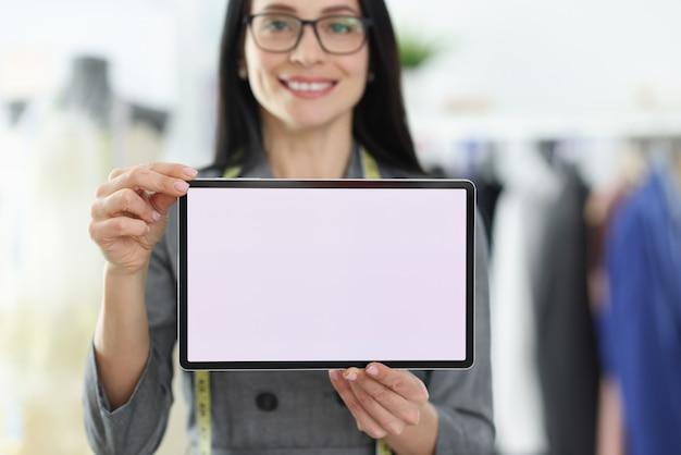 Näherin der jungen frau, die digitales tablett in ihrer handnahaufnahme hält. online-bestellkonzept