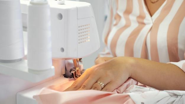 Näherin, die im atelier der nähwerkstatt arbeitet, näht auf overlock-stoffkanten.