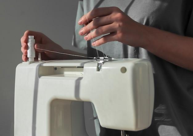 Näherin hände beim aufsetzen der fadenspule auf die nähmaschine