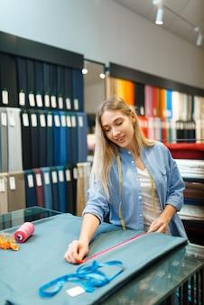 Näherin misst stoffmaterial in textilwerkstatt. frau arbeitet mit stoff zum nähen, schneiderin am arbeitsplatz, schneiderin