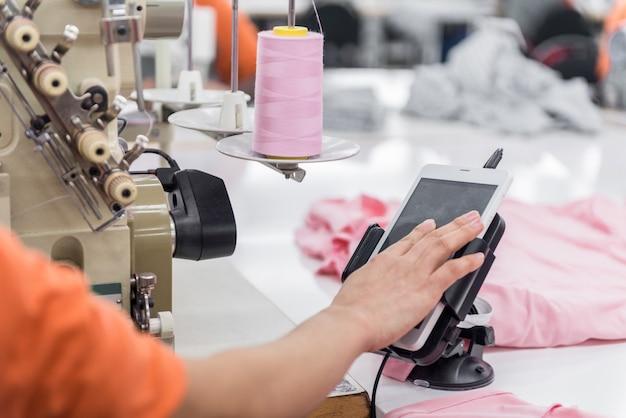 Näherin näht kleidung für die nähmaschine und steuert das tablet. textilwerkstatt. nahaufnahme