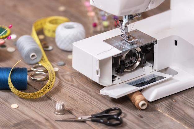 Näherin oder schneiderhintergrund mit nähenden werkzeugen, bunten gewinden, nähmaschine und zubehör.
