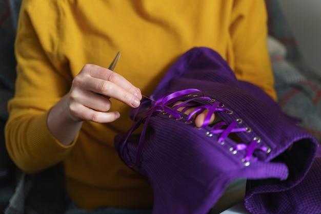 Näherin oder schneiderin, die am korsett arbeitet, während sie an ihrem arbeitsplatz sitzt