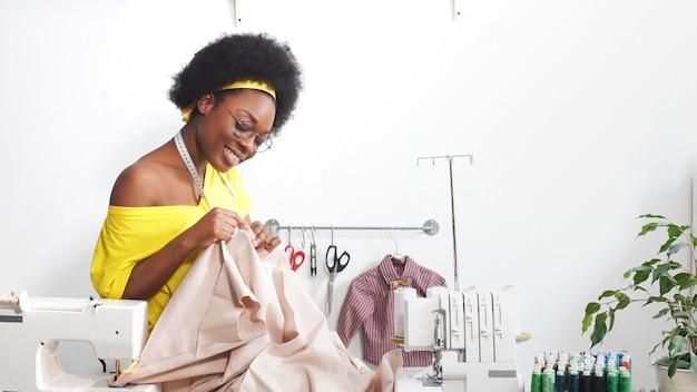 Näherin, schneiderin afroamerikanerin lächelt in die kamera im schneiderstudio. die afroamerikanische frau arbeitet in ihrer werkstatt an selbstisolation.