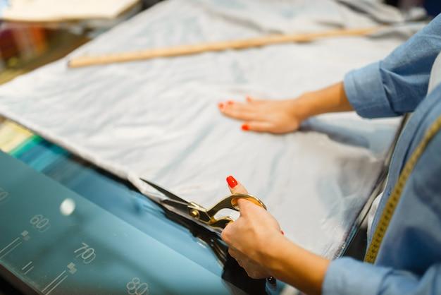 Näherin schneidet stoff mit einer schere im textilgeschäft. frau arbeitet mit stoff zum nähen, schneiderin in werkstatt