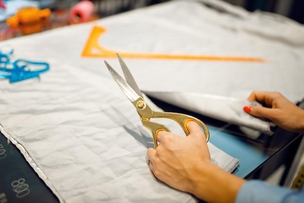 Näherin schneidet stoff mit einer schere in der textilwerkstatt. frau arbeitet mit stoff zum nähen, schneiderin am arbeitsplatz