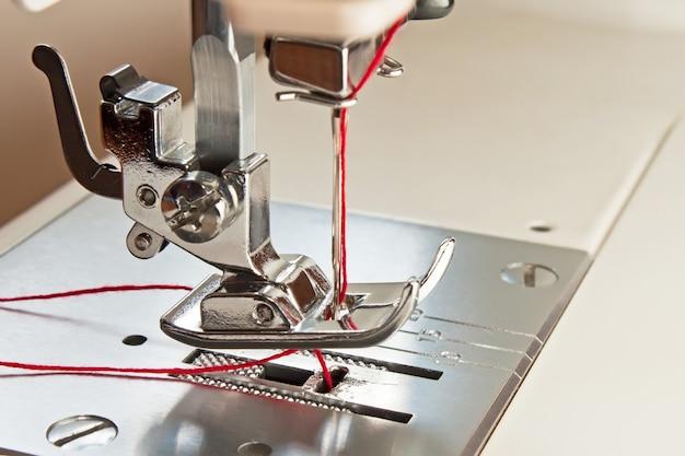 Nähfuß und nadel der nähmaschine mit rotem faden