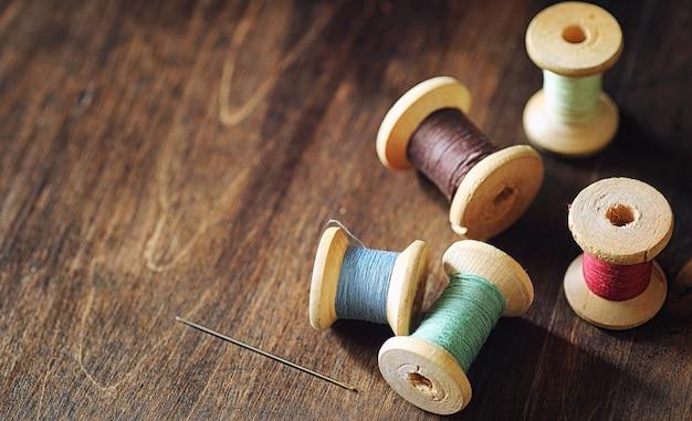 Nähgarn auf einem hölzernen hintergrund. satz von fäden auf spulen im retro-stil. vintage accessoires zum nähen auf dem tisch