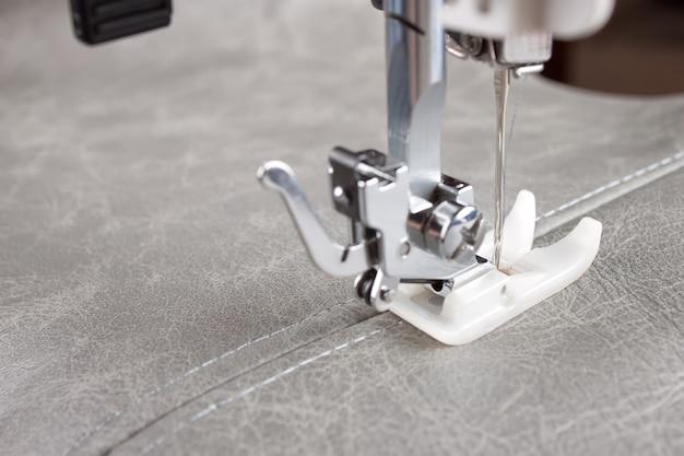 Nähmaschine mit speziellem nähfuß macht eine naht auf grauem leder. nähvorgang hautnah