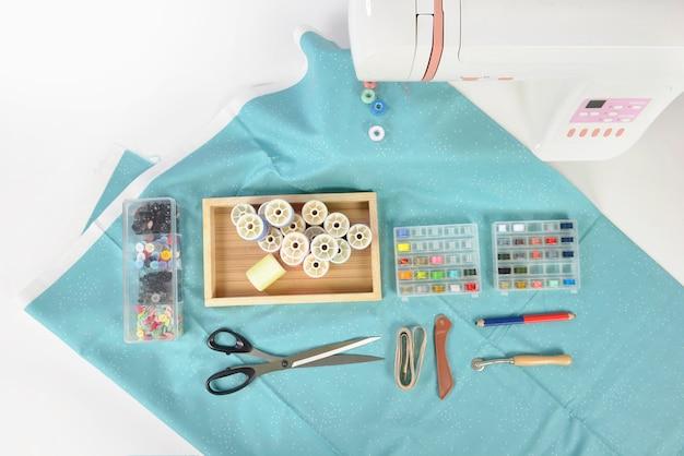 Nähmaschine und bunte garnrollen, schere, stoff und zubehör zum nähen.