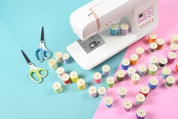 Nähmaschine und bunter faden rollt für das nähen, das nähen und das näharbeitkonzept.