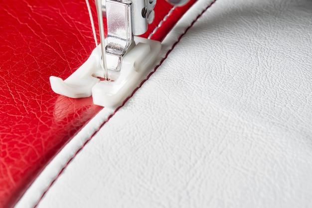 Nähmaschine und weißes und rotes leder mit nahtnahaufnahme