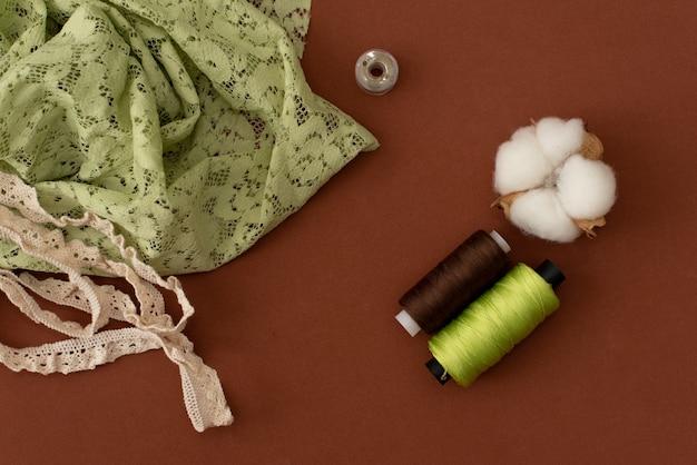 Nähmaschinenspulen mit goldener (messing-) schere und schwarzem, seidigem stoff auf einem alten, schmuddeligen arbeitstisch. schneidertisch. herstellung von textilien oder feinen stoffen.
