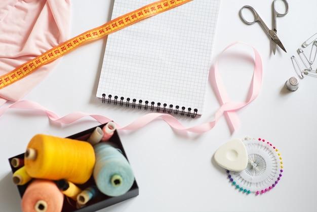 Nähmaterialien - eine schachtel mit fäden in leuchtenden farben, ein rosa band, baumwolle, maßband auf weißem hintergrund. rahmen, platz für text