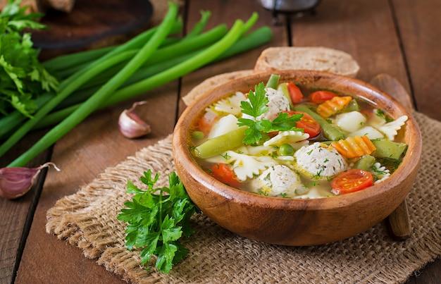 Nähren sie gemüsesuppe mit hühnerfleischklöschen und frischen kräutern in der hölzernen schüssel