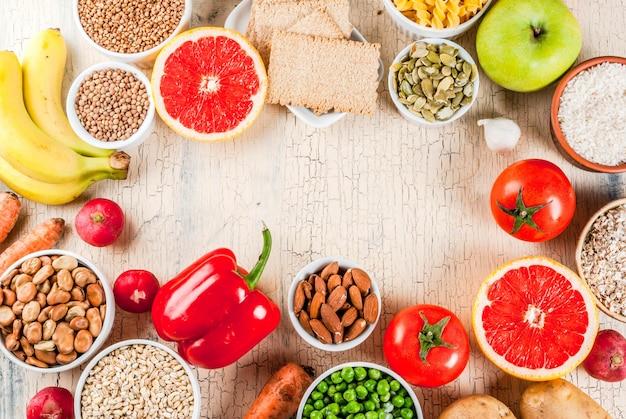 Nähren sie lebensmittelhintergrundkonzept, gesunde produkte der kohlenhydrate (kohlenhydrate) - obst, gemüse, getreide, nüsse, bohnen, heller konkreter hintergrundkopien-raumrahmen oben