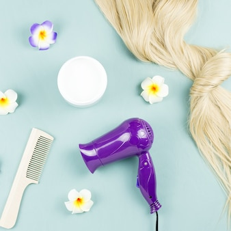 Nährende maske und haarverlängerungen auf blauem holzhintergrund. haarpflegekonzept flach legen