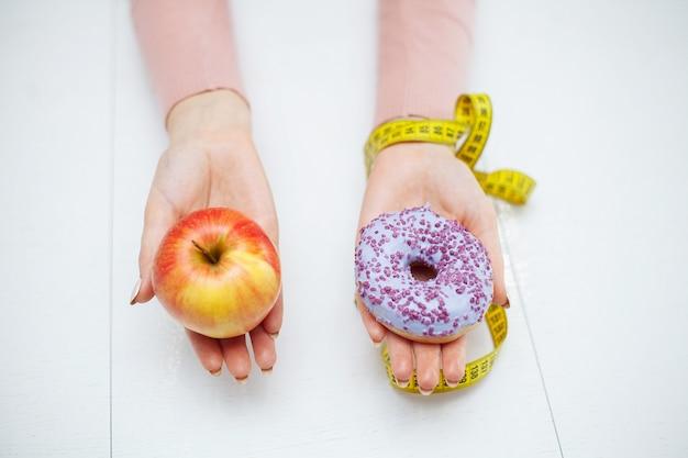 Nährendes konzept, schöne junge frau, die zwischen gesundem lebensmittel und ungesunder fertigkost wählt