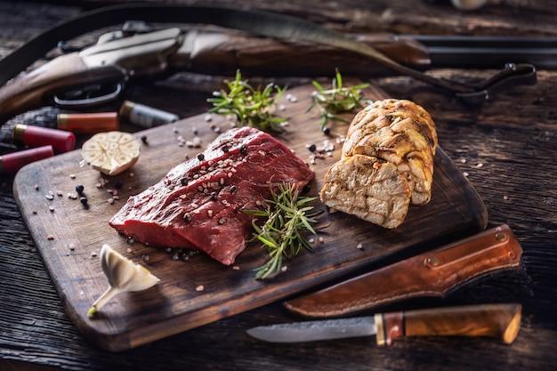 Nährstoffreiches, rohes hirschfleisch zubereitet für einen kochprozess auf einem rustikalen holztisch mit geröstetem knoblauch, rosmarin und jagdzubehör wie schrotflinte und munition