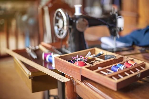Nähwerkzeuge und rollen mit farbfaden auf dem tisch