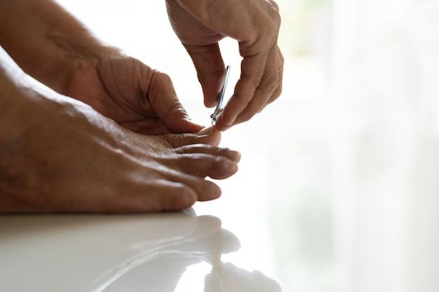 Nagelausschnitt, ältere frauenfuß-ausschnittnägel unter verwendung des nagelknipsers