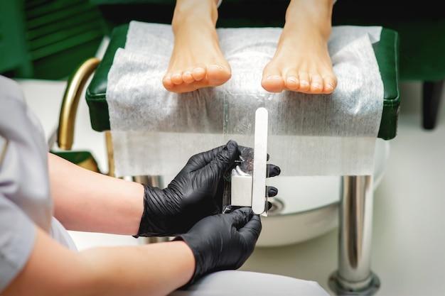 Nagelfeilenwerkzeug in den händen des fußpflegers, bevor das verfahren nägel auf zehen in einem nagelstudio feilt