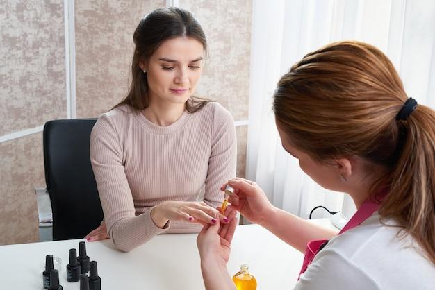Nagelhautpflege. weibliche hand, die öl auf nägel aufträgt