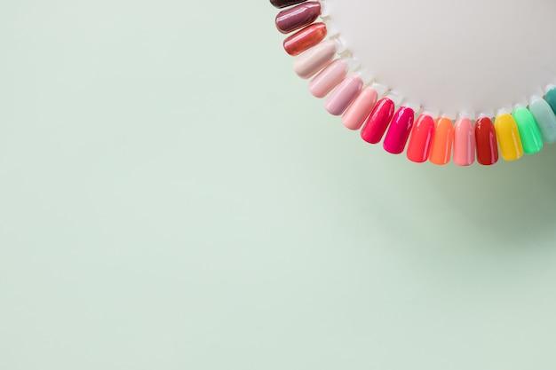 Nagelkunst-designproben auf weichem pastellhintergrund. manikürenagellack-farbpalette. nagellackprüfvorrichtungen in den verschiedenen farben nagelkunst-designrad selektiver fokus. kopieren sie platz