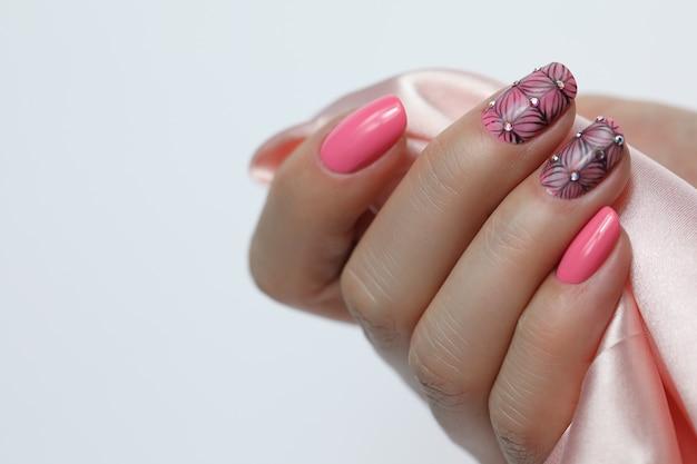 Nagelkunstmaniküre mit erdbeere auf rotem hintergrund. nagelpolitur.