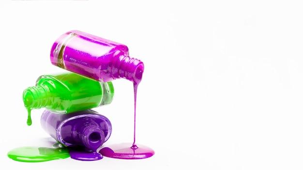 Nagellack, der von staplungsflaschen gegen weißen hintergrund tropft