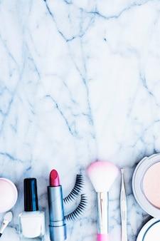 Nagellack; errötet; lippenstift; pinzette; kompaktes pulver und wimpern auf strukturiertem marmorhintergrund angeordnet