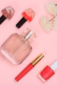 Nagellack, lippenstift, parfümflaschen und blumen auf rosafarbenem hintergrund. damenkosmetik und accessoires. ansicht von oben.