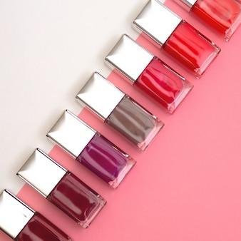 Nagellacke in verschiedenen farben sind auf rosa und weißem hintergrund aufgebaut