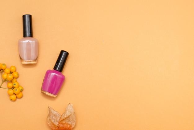 Nagellacke und herbstlaub auf orangem hintergrund. minimalistische flache lage mit kopienraum, draufsicht. modisches kosmetikprodukt. werbung im herbst.