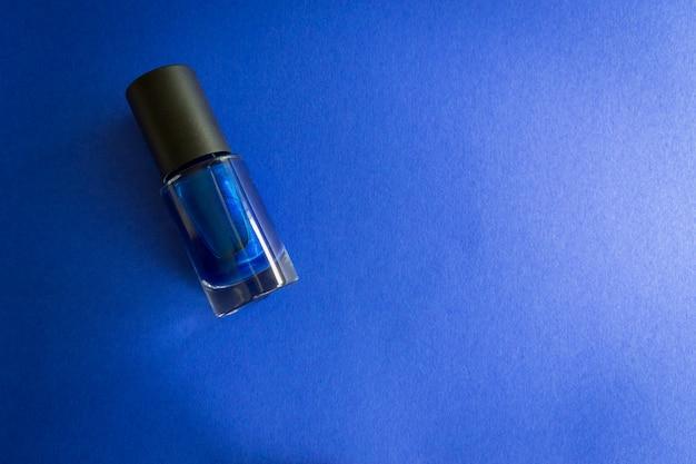Nagellackflasche auf blauem hintergrund. exemplar