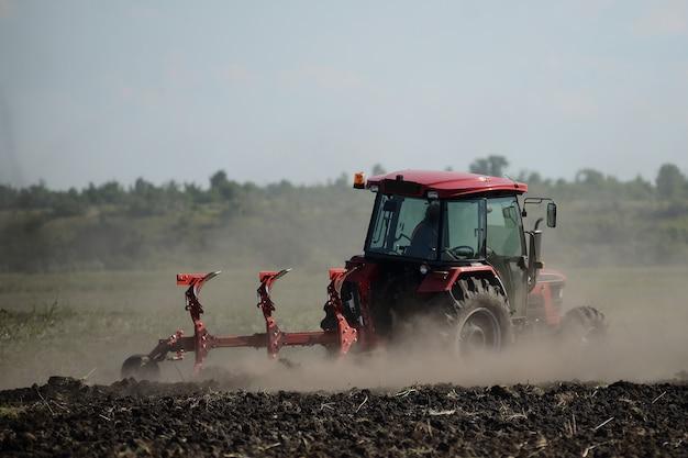 Nagelneuer roter traktor auf der feldfunktion. traktor, der boden kultiviert und ein feld für das pflanzen vorbereitet