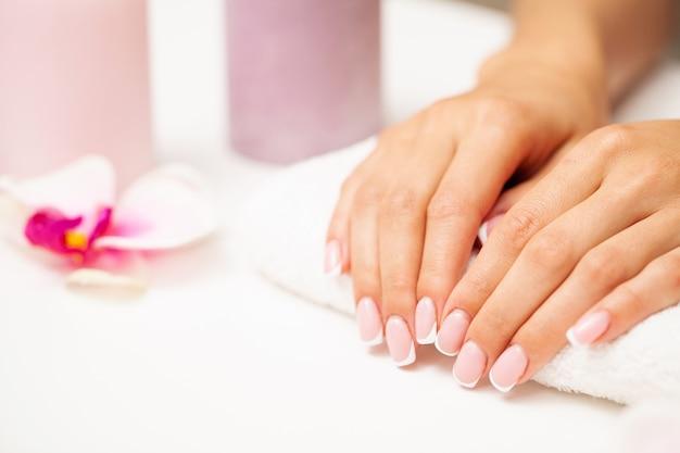 Nagelpflege, frau demonstriert eine frische maniküre in einem schönheitsstudio