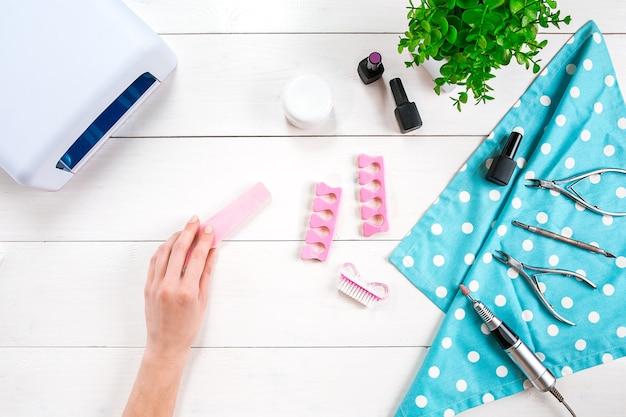 Nagelpflege. maniküre-set und nagellack auf holzuntergrund. ansicht von oben. maniküre. maniküre für dich