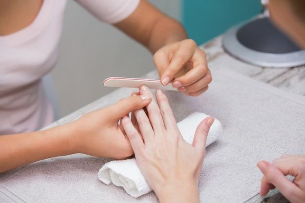 Nageltechniker, der dem kunden maniküre gibt