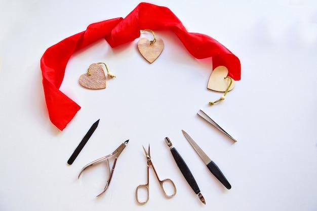 Nagelzubehör und herzen zum valentinstag. kauf von maniküreprodukten. maniküre für den 14. februar. besuch eines schönheitssalons in den ferien. isoliert auf einem weißen hintergrund
