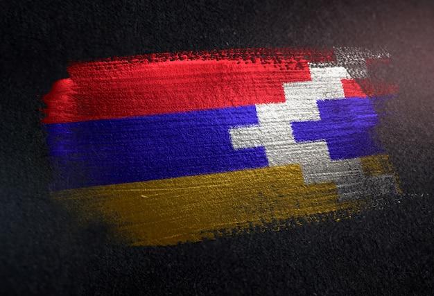 Nagorno-karabakh-republik-flagge gemacht von der metallischen bürsten-farbe auf dunkler wand des schmutzes