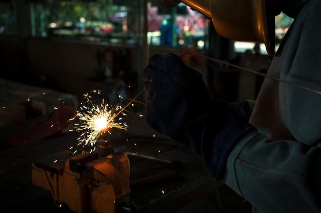 Nahansicht. arbeitskraftschweißer, der schweißgasstahl in der industrie mit sicherheitsmaskenhandschuhen und -sicherheitsausrüstung bearbeitet.